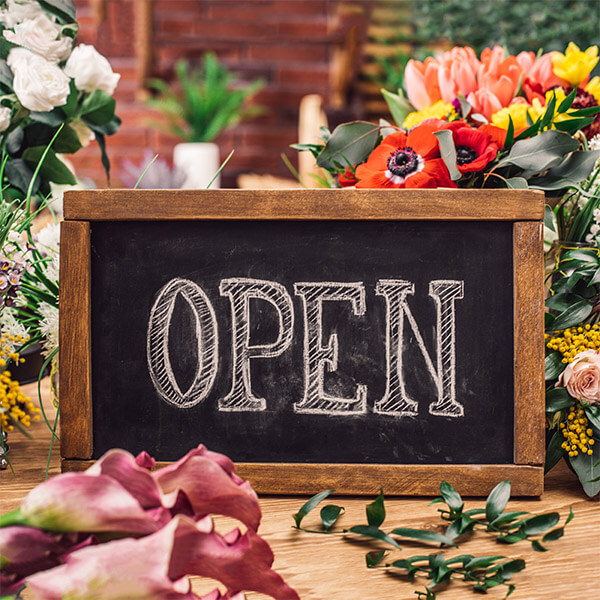 Open sign on table with flowers